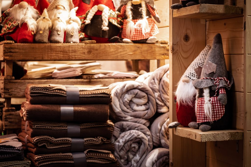 wool toys and a stack of wool blankets at a christmas market at night