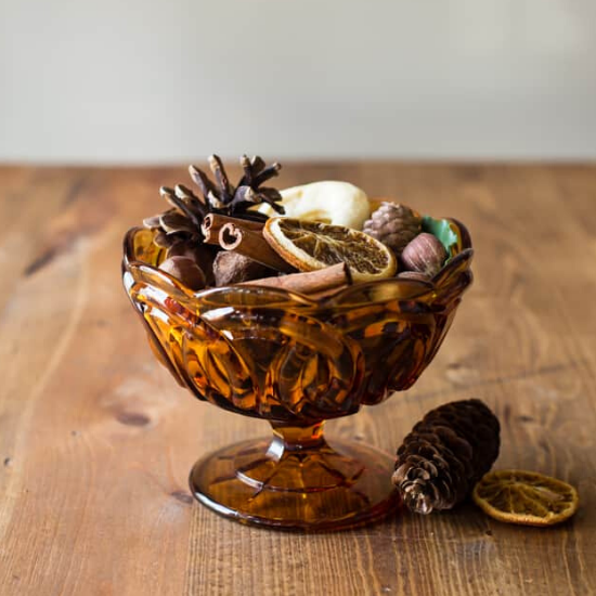 Amber colored glass bowl filled with homemade fall potpourri on a wooden table.