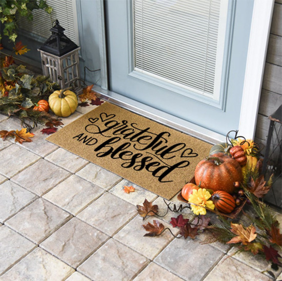 "Jute front door mat that says ""grateful & blessed"" placed in front of a door surrounded by a lantern and fall decor."