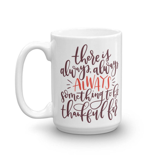 "White, porcelain mug with hand lettering that says ""there is always something to be thankful for""."