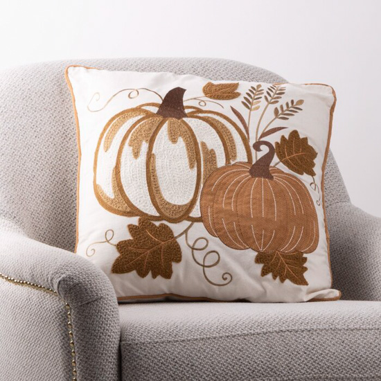 Oatmeal colored armchair with embroidered pumpkin throw pillow.