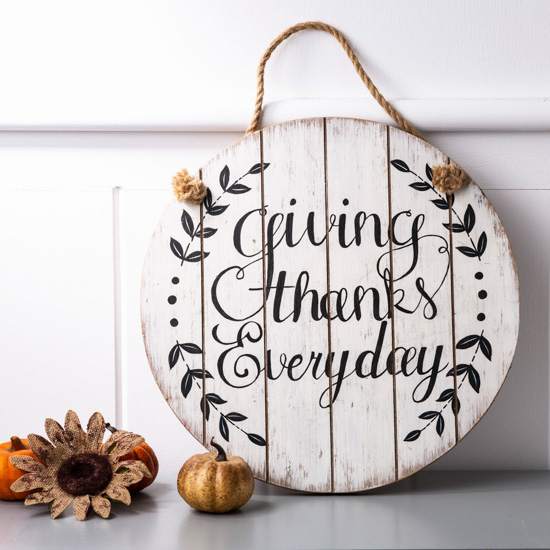 "Round wooden sign with a rope loop for hanging that says ""giving thanks everyday."""