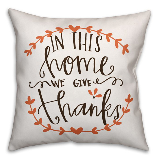 "White throw pillow, handwritten saying ""in this home we give thanks""."
