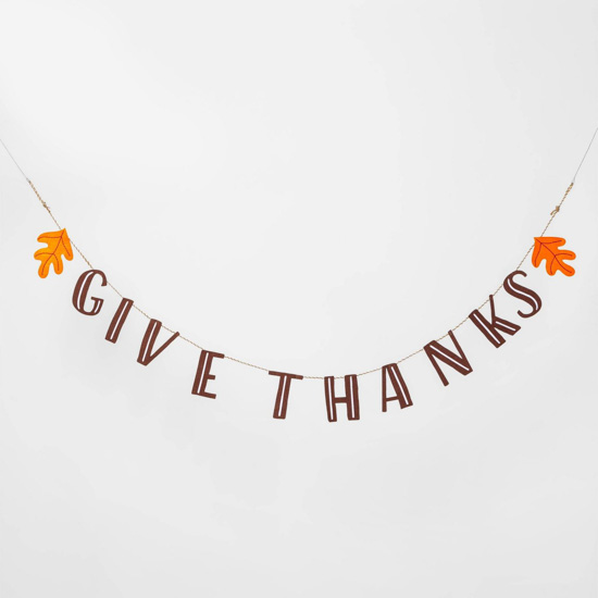"Simple banner that says ""give thanks"" bookended by orange fall leaves."