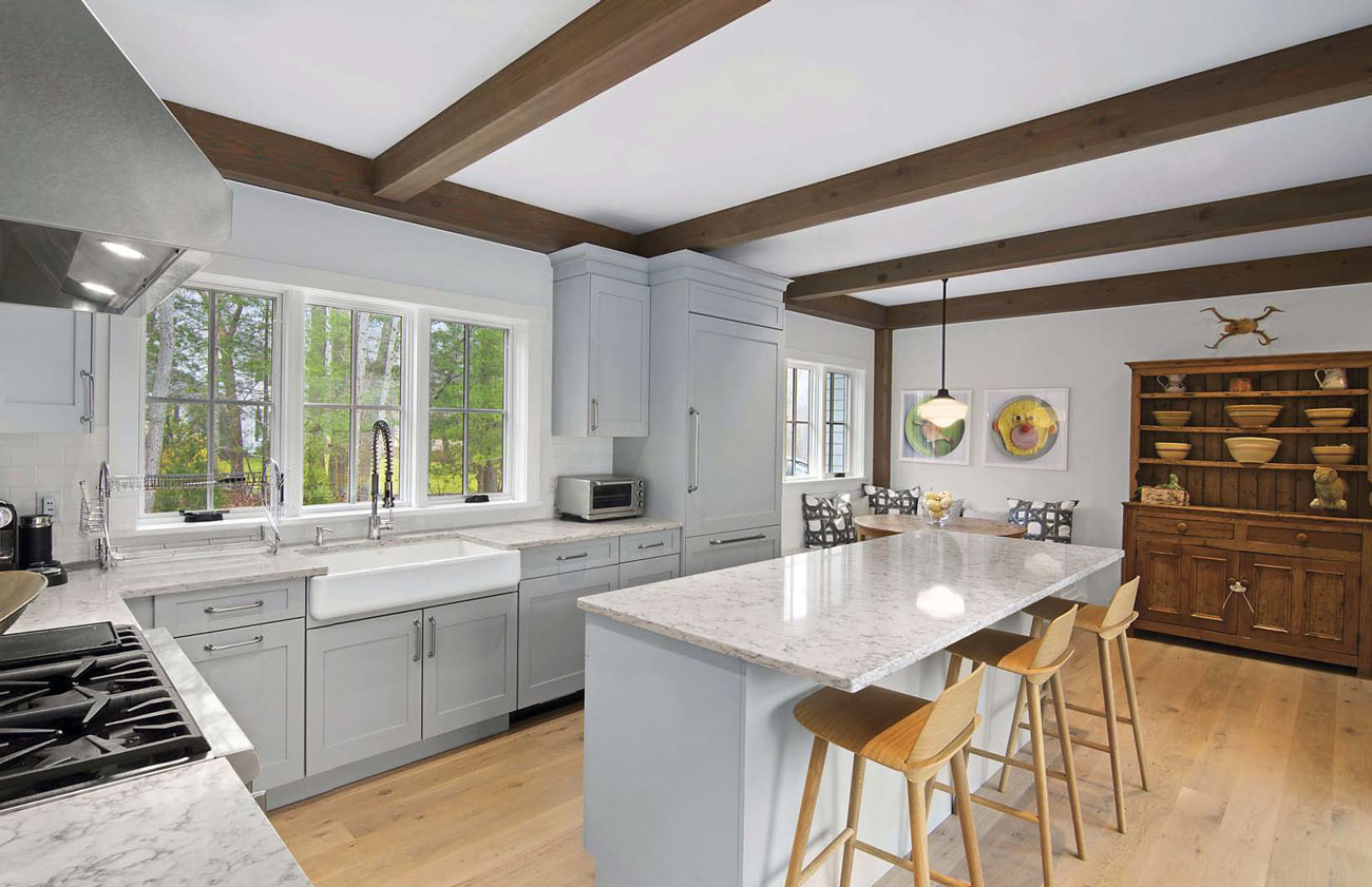 Large gray toned open-concept kitchen with bar/island seating and over looking a dining nook with wooden exposed beams and a large wooden hutch.