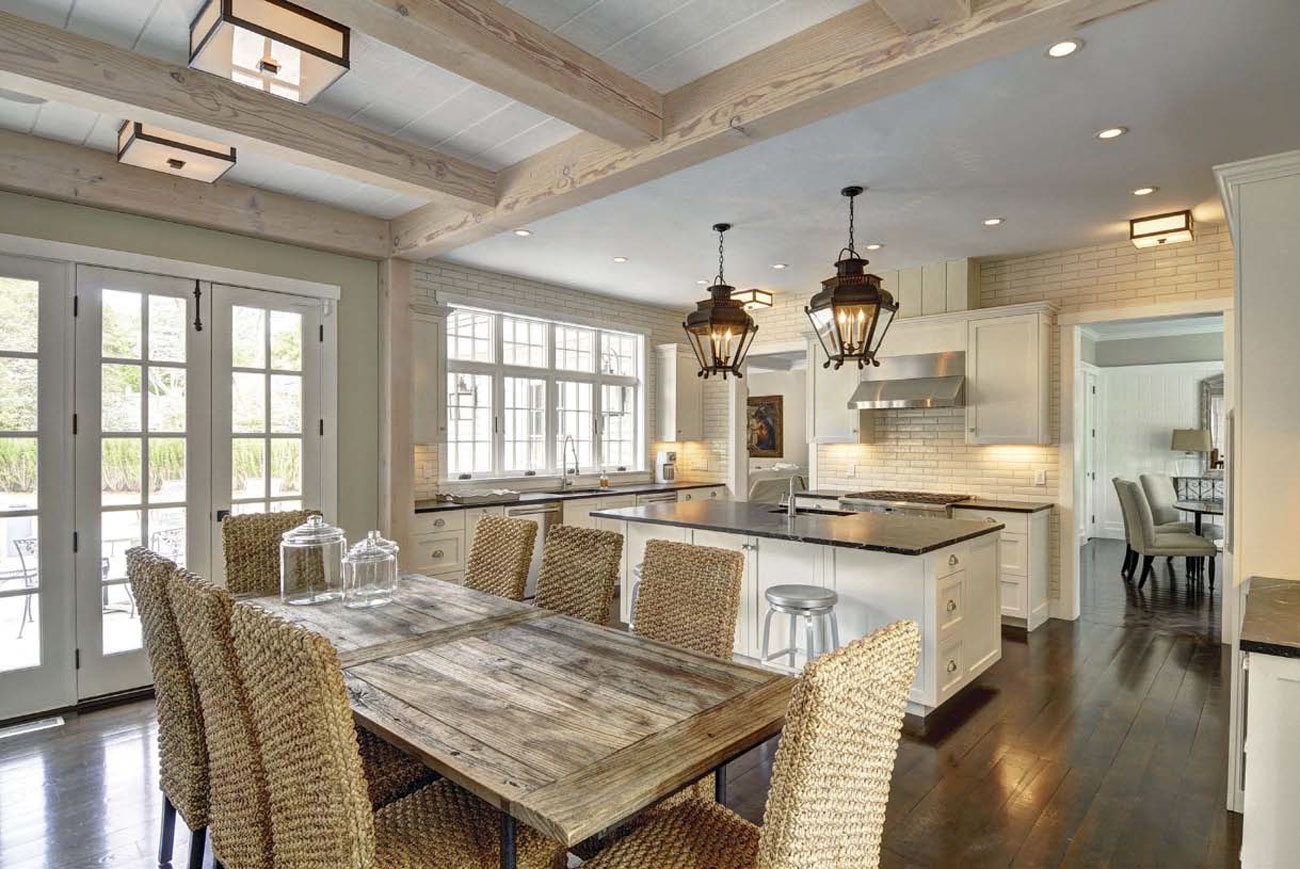 Expansive dining area and kitchen with exposed light colored beams and antique styled pendant lights hanging over the island.
