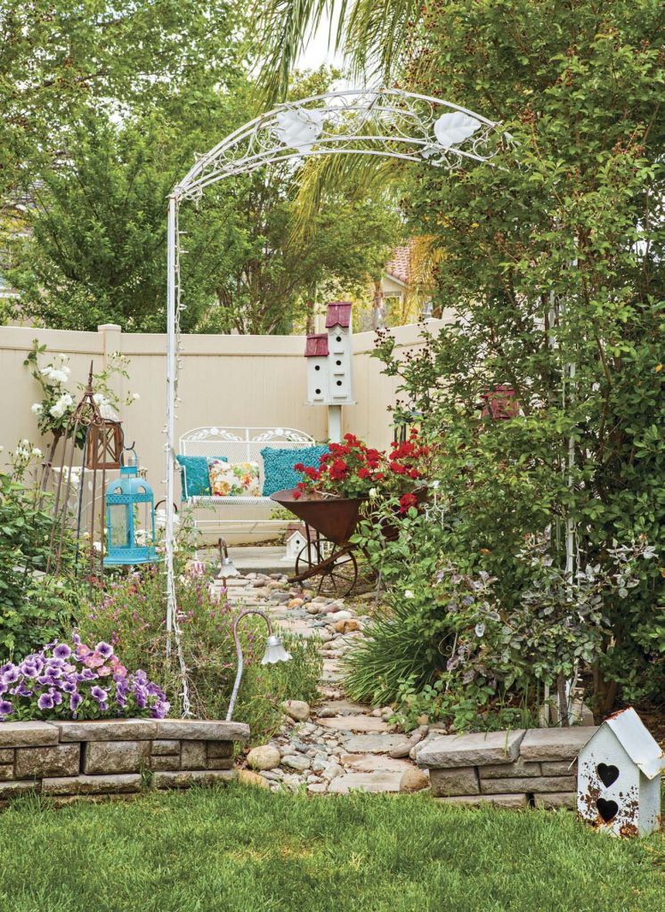 White metal arbor leading to a stone path to an outdoor sitting area with a rustic wheelbarrow filled with red geraniums.