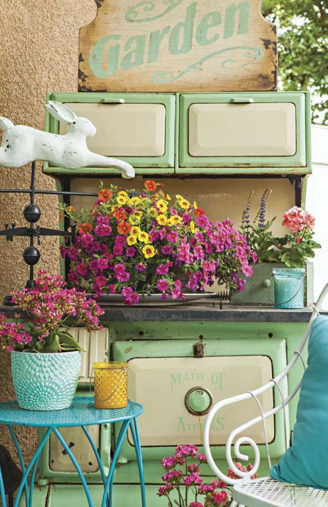 Back porch with a vintage mint green stove surrounded by flowers and an iron seating set.