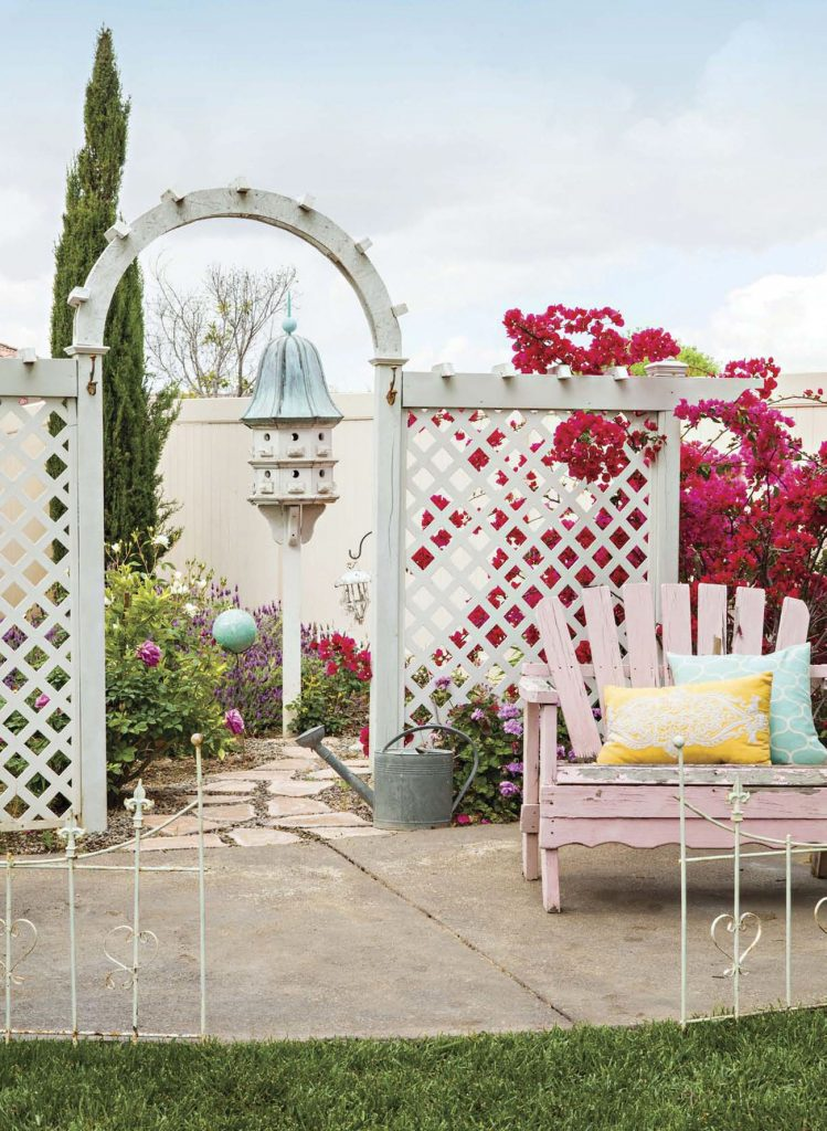 White wooden latticed arbor with climbing pink bougenvilla and a rustic pink adirondak chair in a backyard.