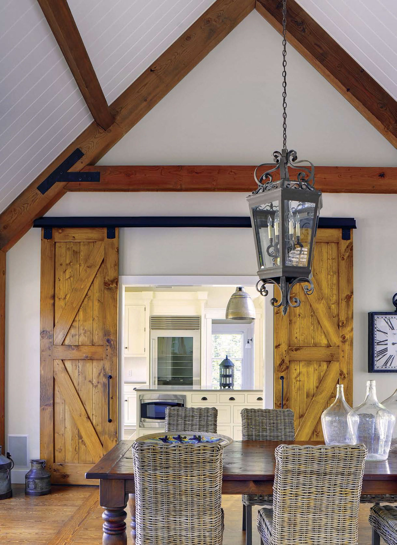 A pitched ceiling with exposed beams and a large lantern pendant hanging over the dining room with sliding barn doors that open to the kitchen.