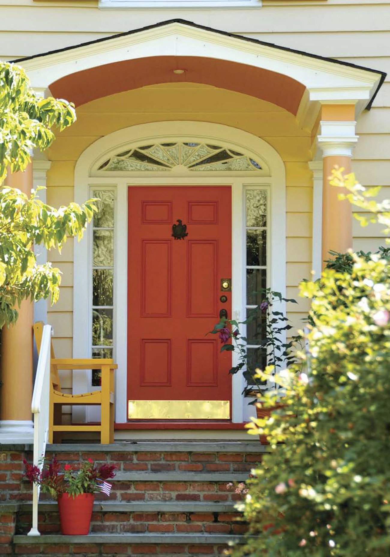 Brick front steps to a small porch with a red door surrounded by panes of glass.