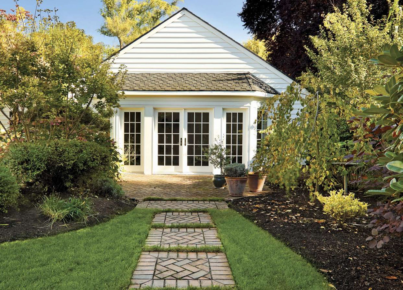 Custom brick pavers create a path through the garden toward a back house.