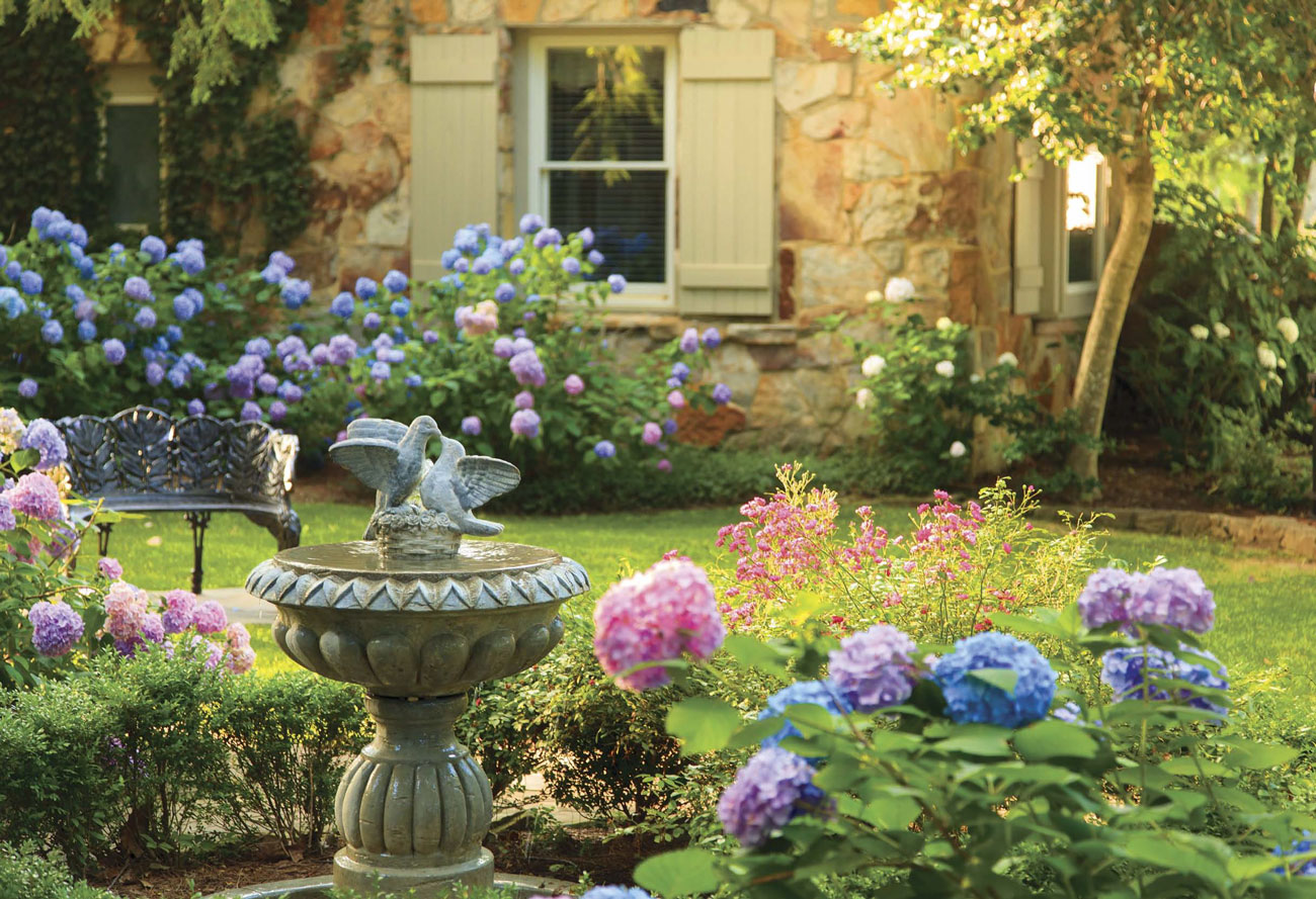 Concrete bird bath surrounded by pink, purple and blue hydrangeas and a wrought iron garden bench.