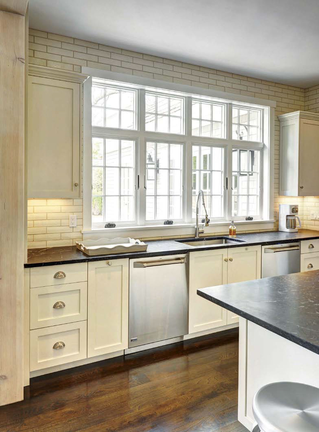 Photo of a kitchen over the island toward the kitchen sink and windows for a gorgeous view.