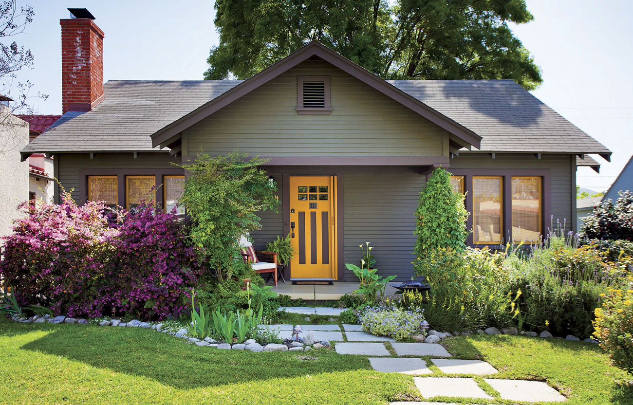 Home exterior of a muted green bungalow with stone pavers up to a bright yellow front door.