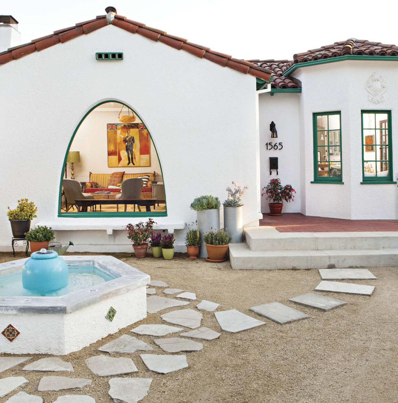 Front yard view of a Spanish bungalow with stone walkway and a fountain feature.