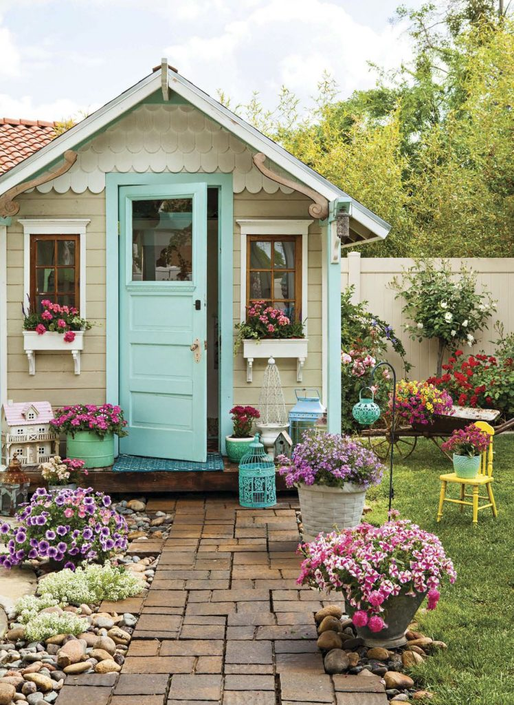 Vintage style playhouse in a yard surrounded by colorful potted flowers and a brick pathway.