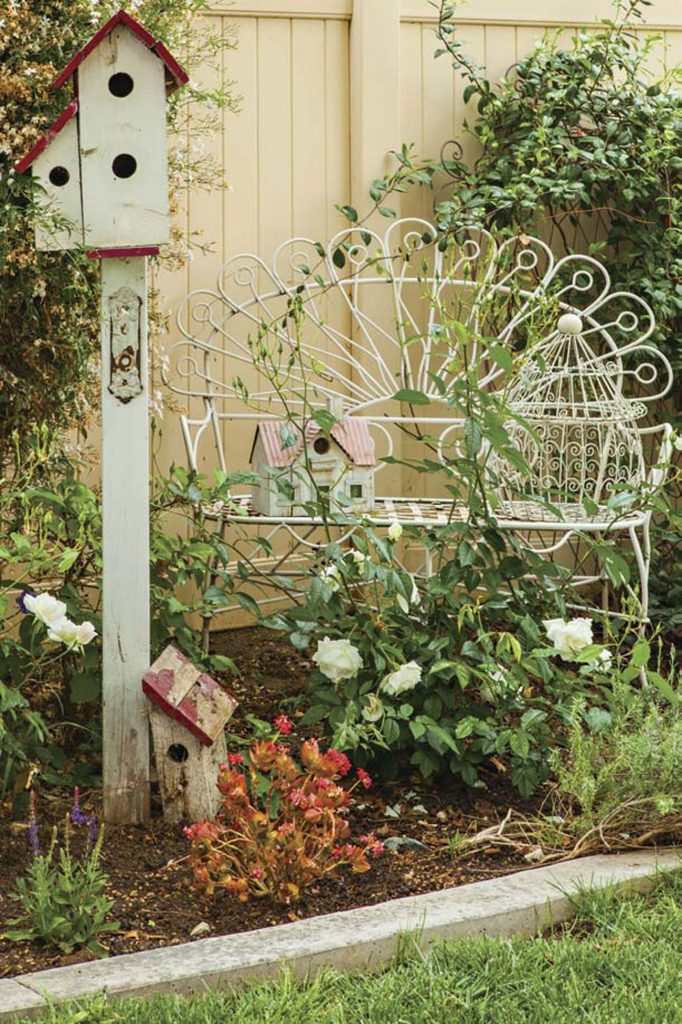Wrought iron white peacock bench and rustic birdhouses in a garden.