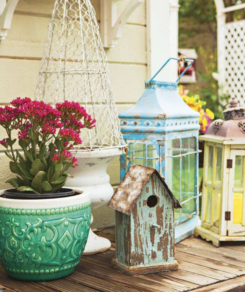 An outdoor collection of lanterns and birdhouses with colorfully distressed finishes.