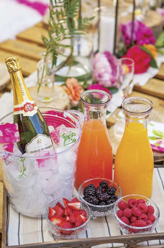 A bright and colorful mimosa bar with champagne on ice and fresh juices and fruit to garnish.