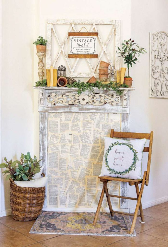 Rental style faux mantle filled with paper book pages next to a wooden folding chair and woven basket filled greenery.