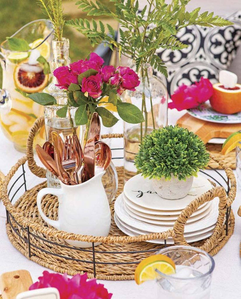 Woven tray used as a centerpiece with fresh flowers, small plates, vases and cutlery.