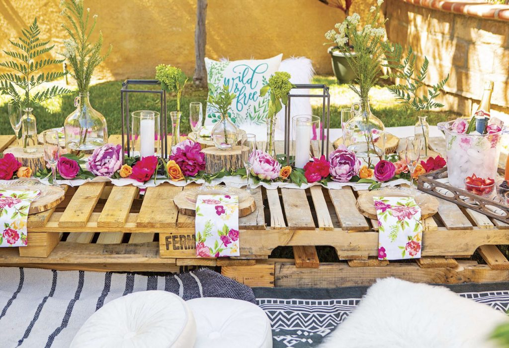 Garden party set up with a custom outdoor table made of wooden pallets and topped with bright pink and purple florals, greenery and lanterns.