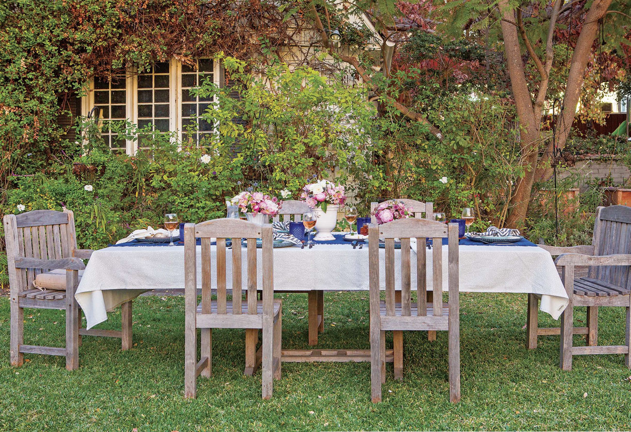 long table with 6 chairs, white and blue linens and floral arrangements in a garden