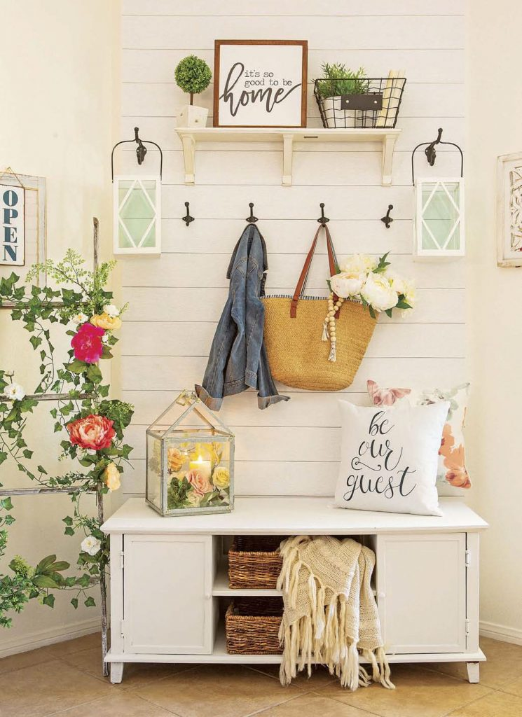 Custom shiplap up the wall behind a bench to create a faux entryway with hooks for purses and jackets.