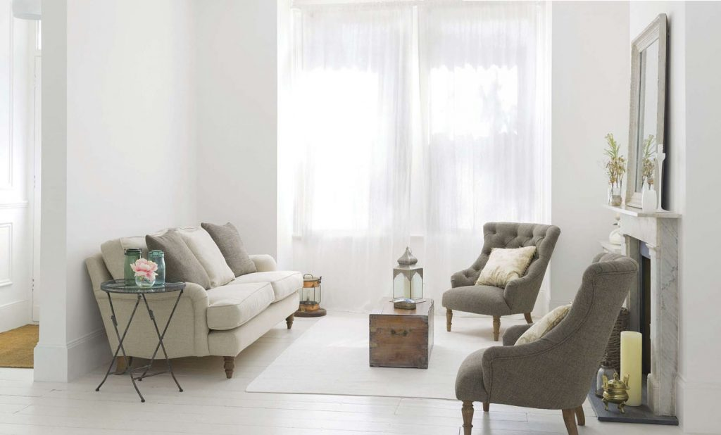 Bright white modern cottage living room with a natural colored couch and twin tufted gray chairs.