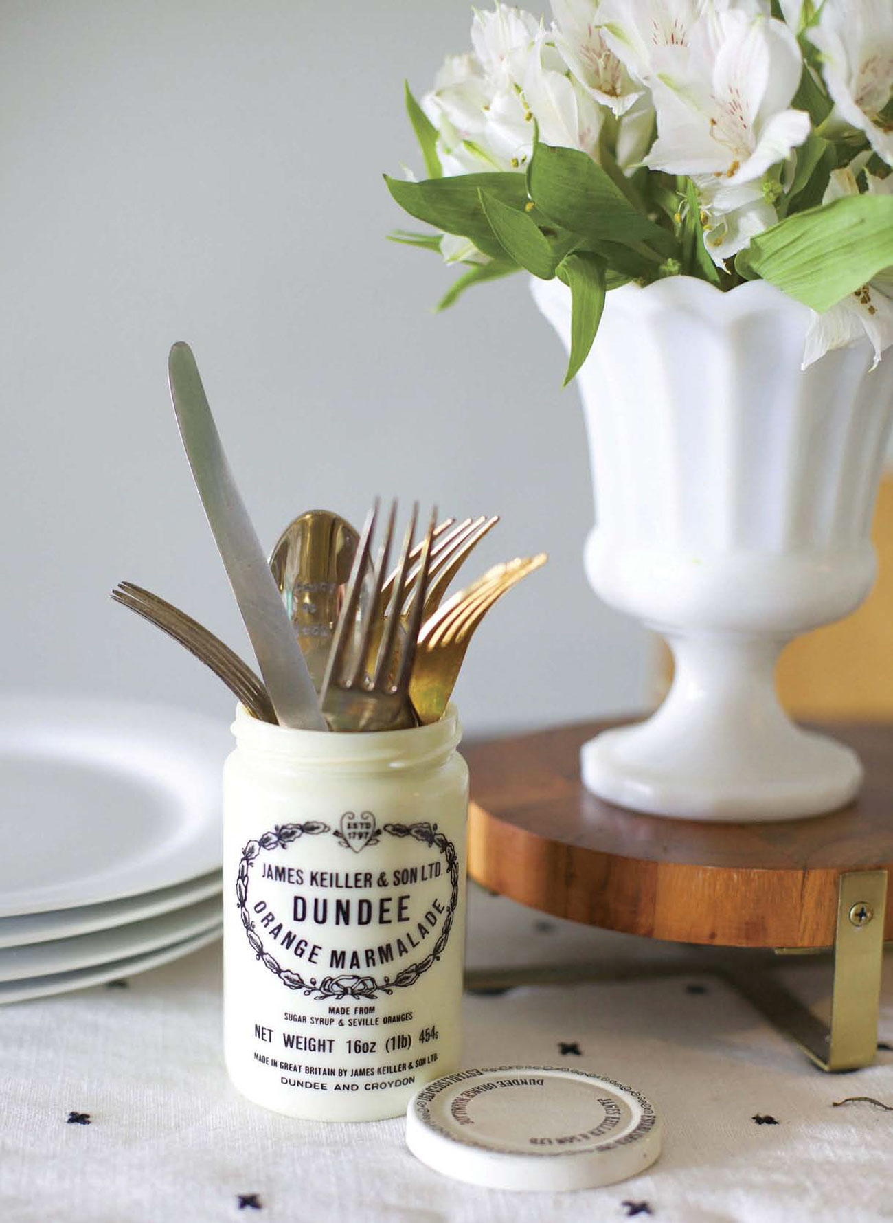 Keiller Dundee marmalade jar filled with silverware on a dining table next to white plates and a white vase of flowers.