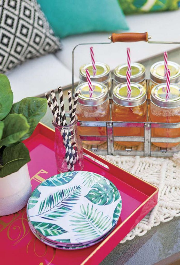 Bright colorful trays and mason jars with cocktails and striped straws loaded into a vintage-style beverage caddie.