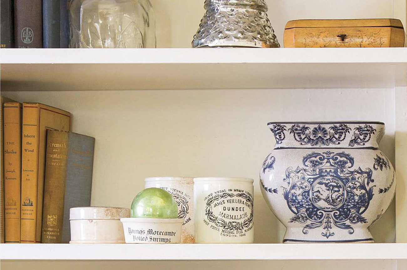 Keiller Dundee marmalade jars arranged on a shelving space alongside books and antique vases.
