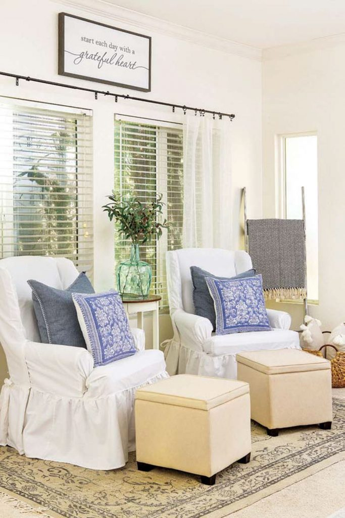 White draped armchairs with matching denim blue pillows and square cream colored ottomans.