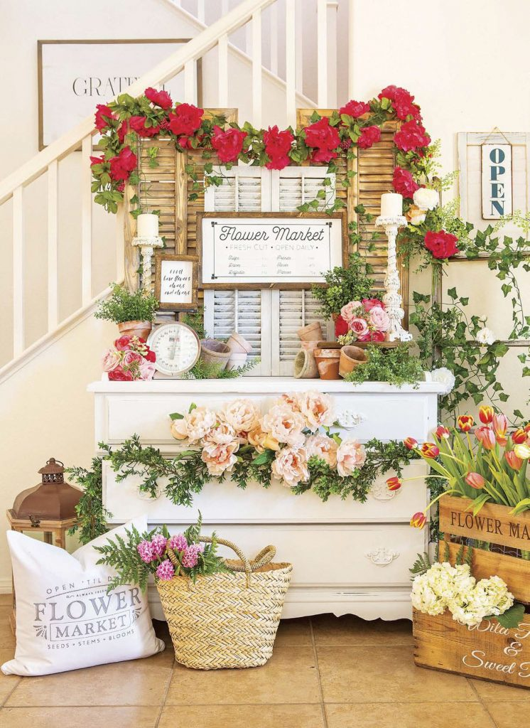Faux flower market made up of a white dresser and shutters and a copious amount of fresh flowers.