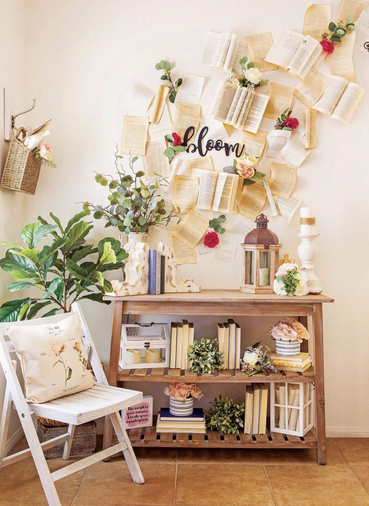 "A folding, white wooden chair next to a magical looking ""book wall"" with seemingly flying books and pages making an art installation moving up the wall."