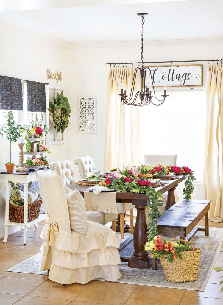 Cottage dining room with farmhouse table with wooden bench and fabric covered chairs surrounded by fresh flowers.