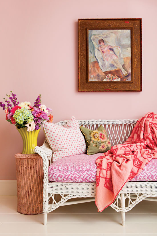 Pink bedding and a pink statement wall with vintage art hanging on the wall and a white whicker daybed.