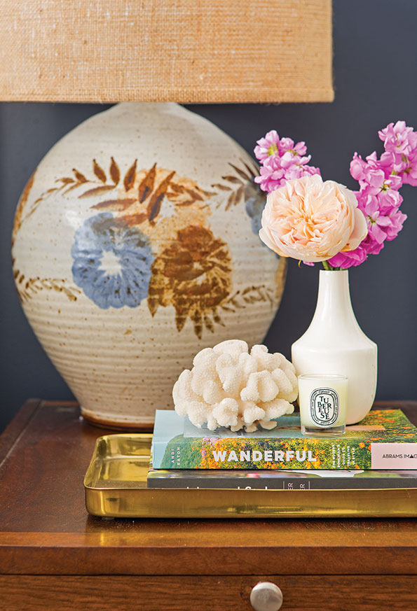 Mid-century side table topped with a mix of vintage and new decor with fresh flowers and vintage lamp.