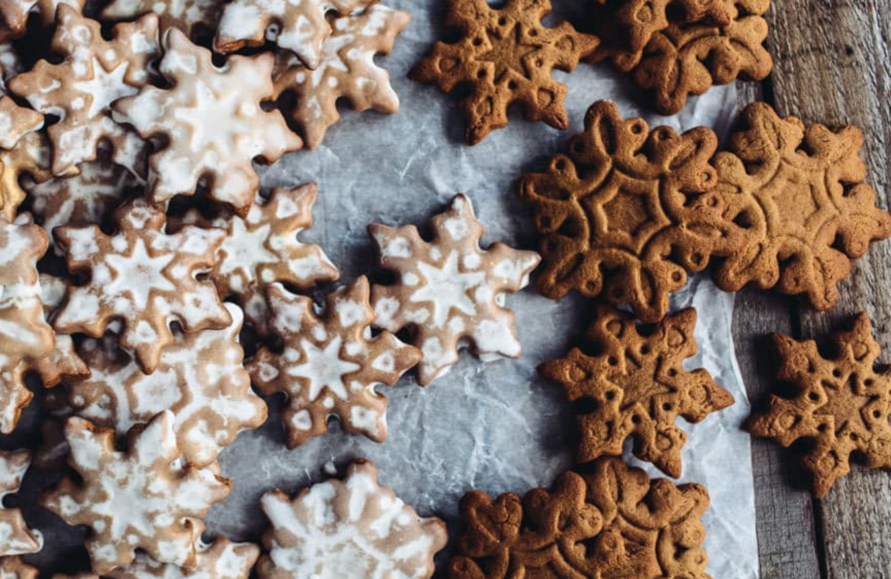 Snowflake shaped gingerbread cookies in different sizes and some with white glaze on top.