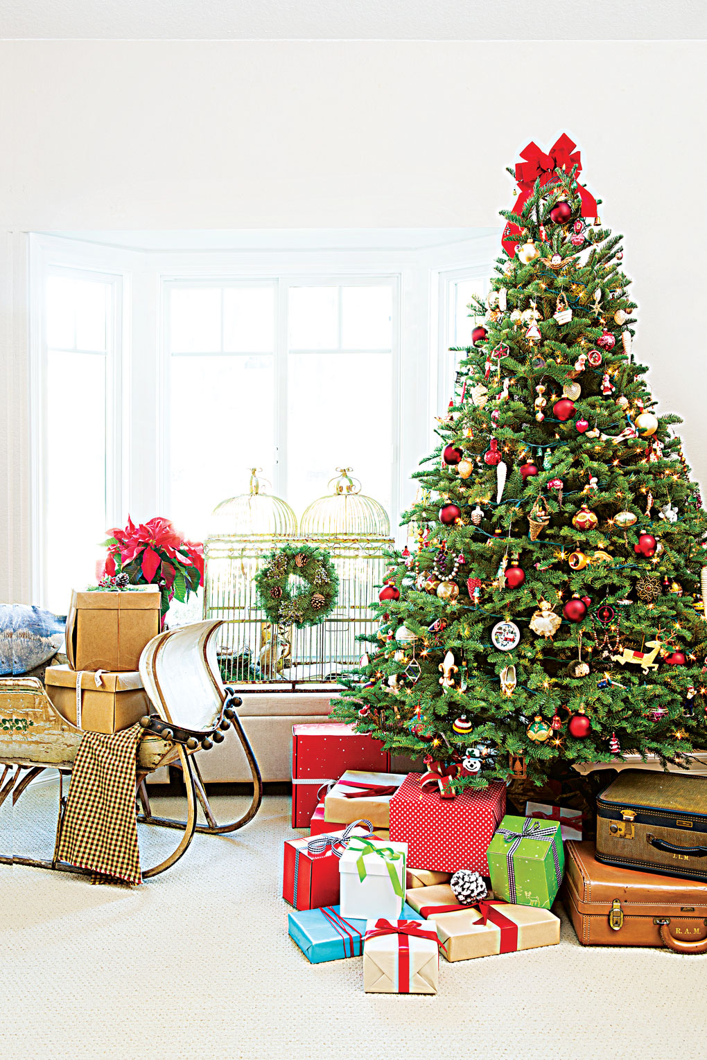 A large and lovely decorated Christmas tree topped with a red bow and surrounded by vintage suitcases and wrapped gifts all next to a vintage sleigh.