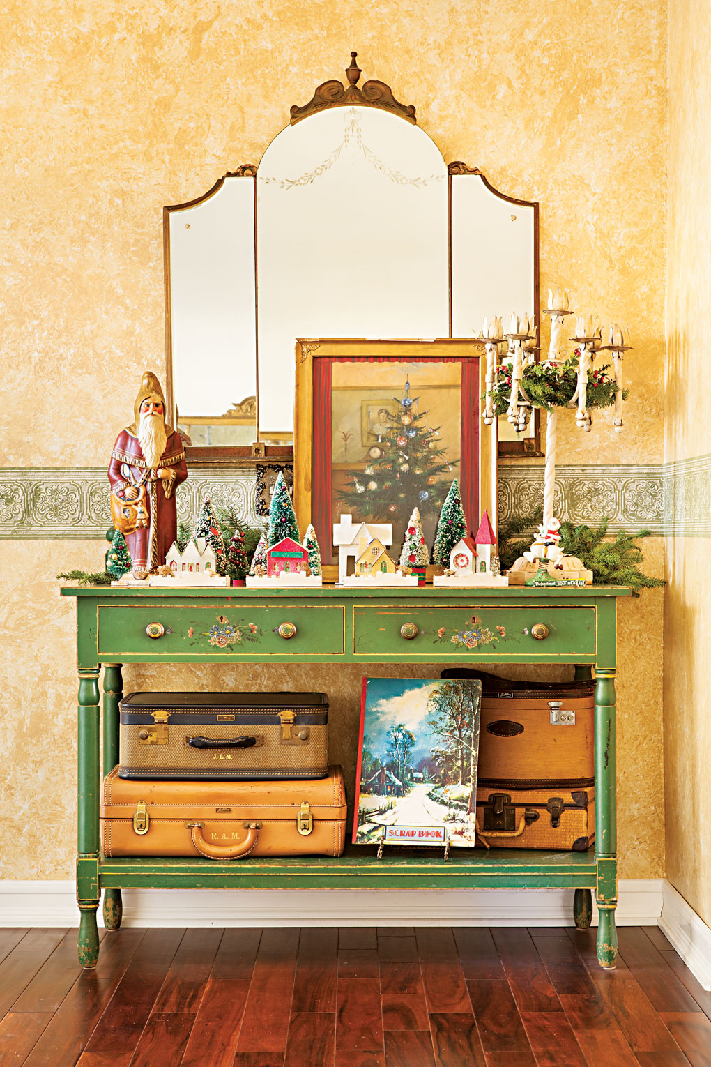 A vintage green entryway table adorned with a village of bottlebrush trees and putz houses next to an elegant candelabra.