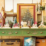 green antique sideboard with christmas collectibles displayed on top