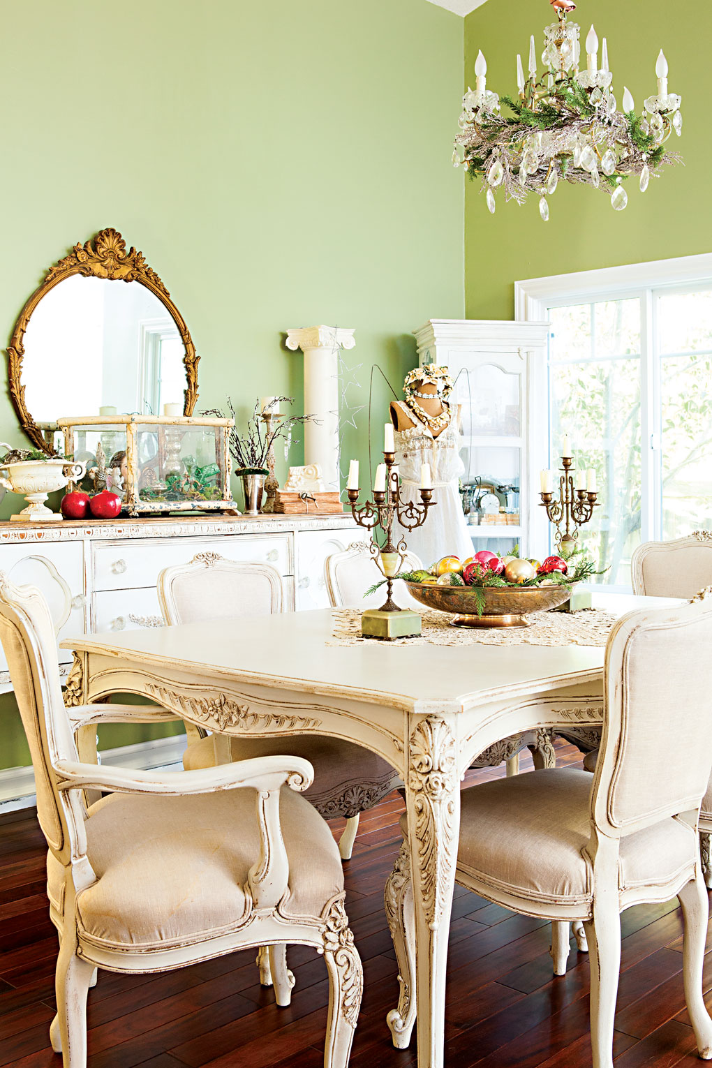 Light green walls surround a vintage white dining set with a hutch behind it.
