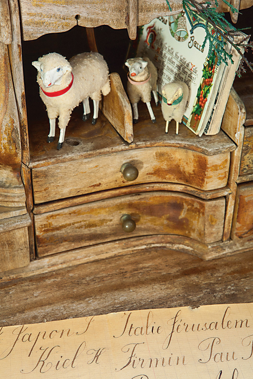 Vintage cabinet decorated with German Putz Sheep and Christmas postcards.