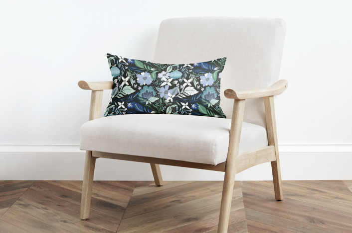 modern white and tan armchair with a blue floral pillow.