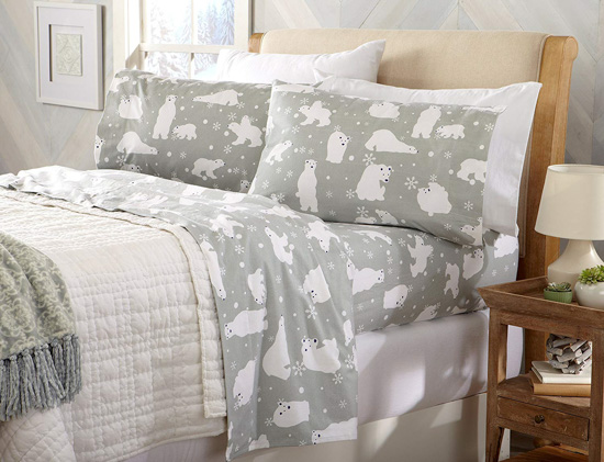 Wooden bed frame made up with white comforter and gray flannel sheets.