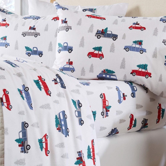 White flannel bedding covered with red and blue colored cars with Christmas trees tied to the top.