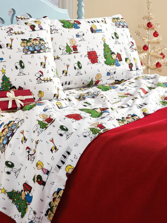 Light blue bed frame with a bed made up with a red comforter and caroling Peanuts characters on the flannel sheets.