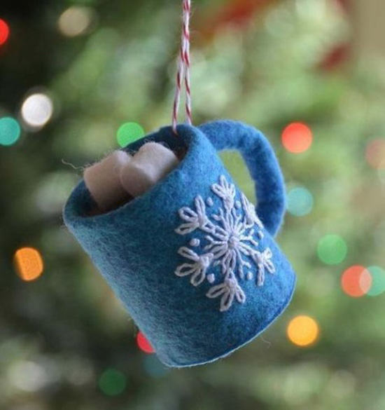 Homemade ornament that looks like a blue mug filled with cocoa and marshmallows hanging from a Christmas tree.